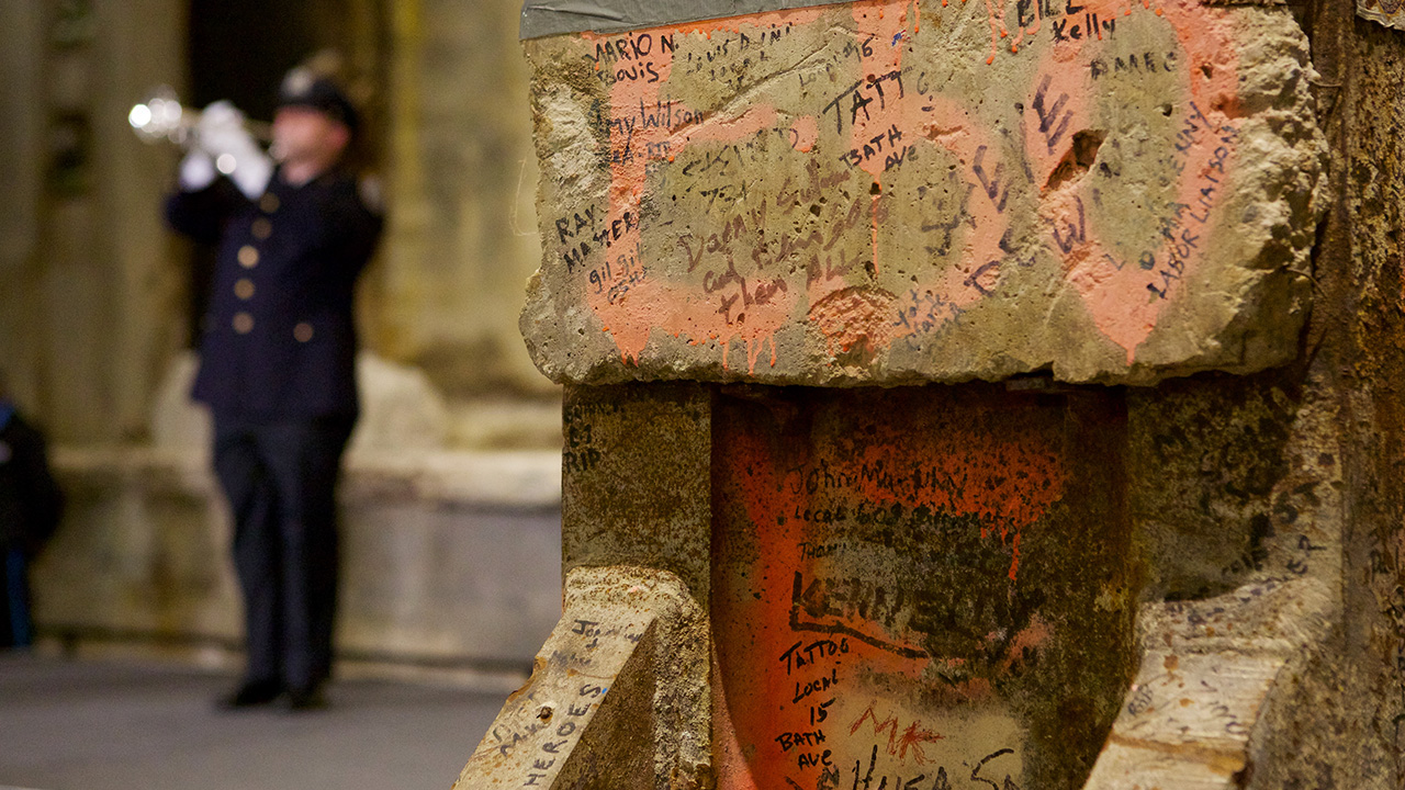 Dozens of names are seen up close on the concrete Last Column. The concrete is worn and sprayed with orange paint. A man in a blue uniform and white gloves plays a trumpet in the distance.