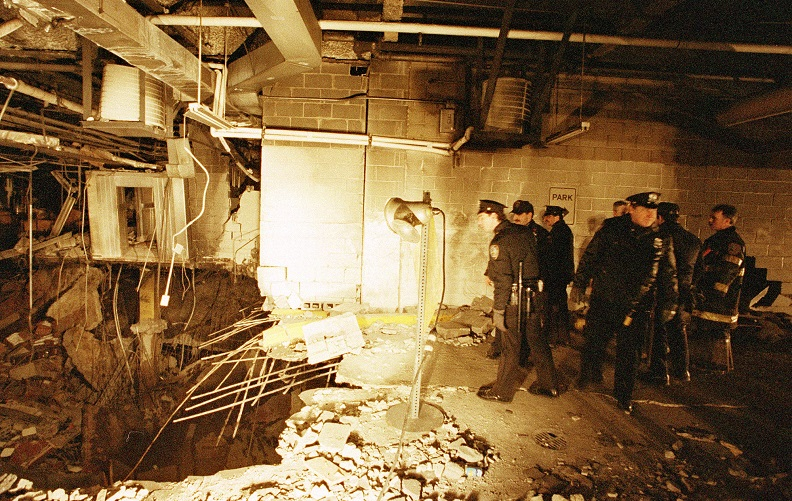 A historical photo of the 1993 World Trade Center bombing shows officers inspecting the crater left by the blast. The officers are standing to the right and looking down at  twisted rebar and crumbled concrete to the left