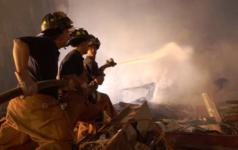 A historical photo from Ground Zero shows three firefighters hosing down a smoky pile of debris at night. A flood light illuminates the smoke and partially silhouettes the three firefighters.