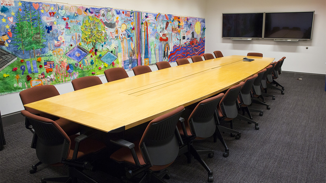 Red-cushioned rolling chairs surround a long, wooden conference table. A colorful mural of children's artwork is on the wall.