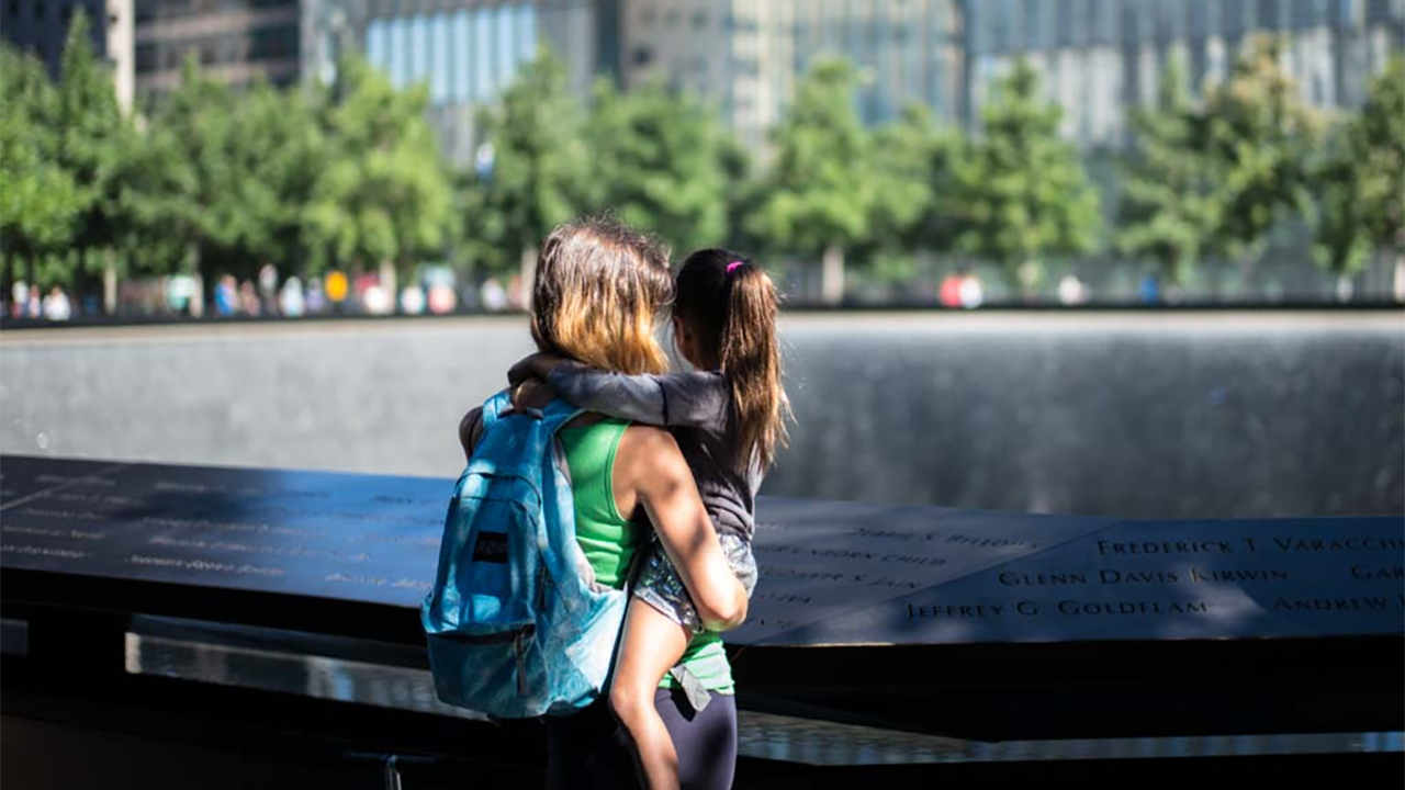 A woman with a backpack holds a young girl with a ponytail as they both look at one of the Memorial's reflecting pools on a sunny day. Green oak trees and buildings are seen farther afield.