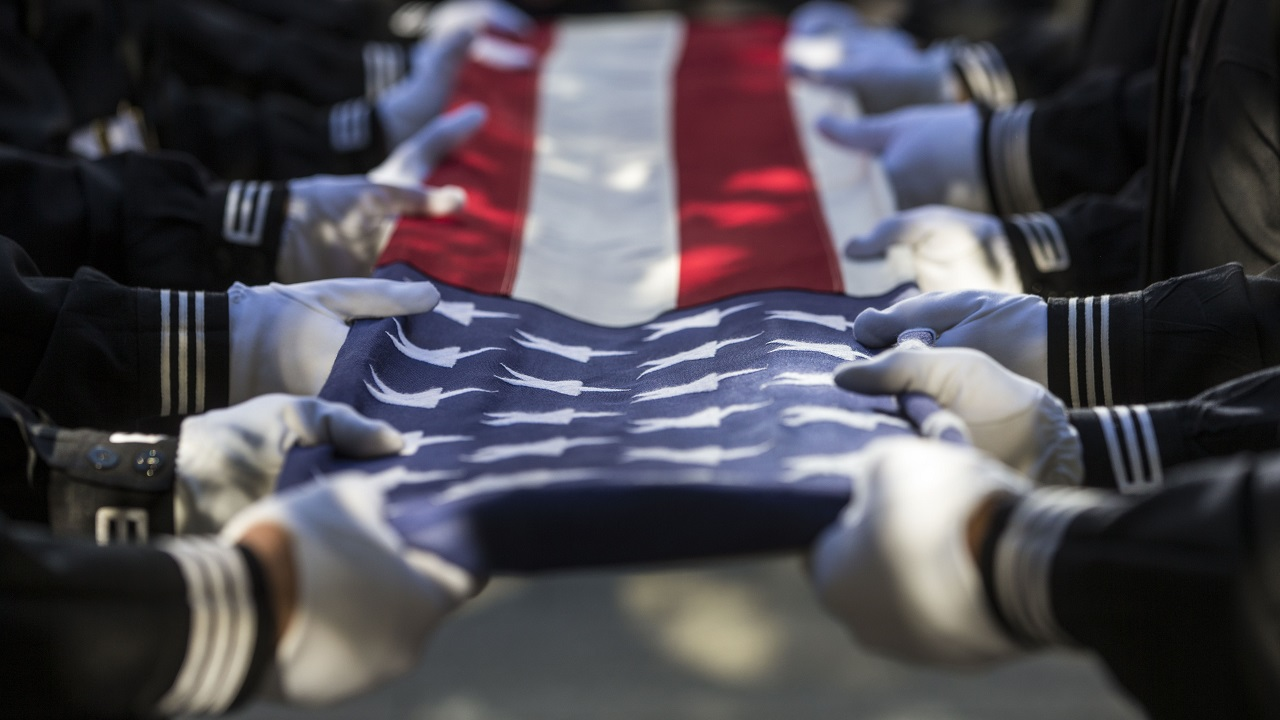 The white-gloved hands of people in black uniforms grip a folded American flag during a ceremony. Spots of sunlight and shadows fall on the flag.