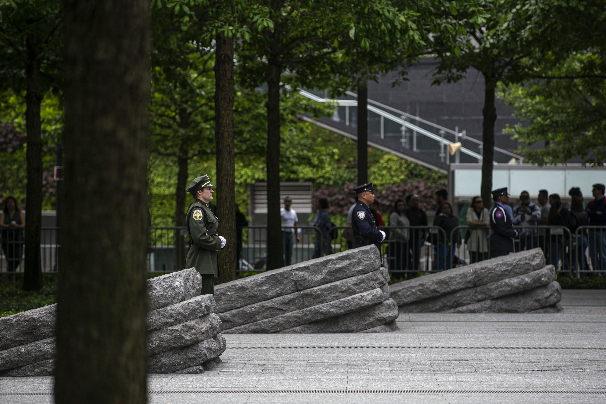 Three officials in formal uniforms stand beside three granite monoliths at the Memorial Glade. A crowd of people has gathered in the shade of trees behind them.