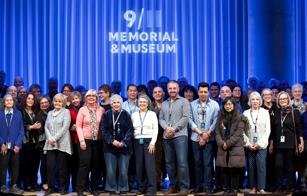 A crowd of about two dozen volunteers smile onstage at an event in the Auditorium. The logo of the 9/11 Memorial & Museum is projected on a blue stage curtain behind them.