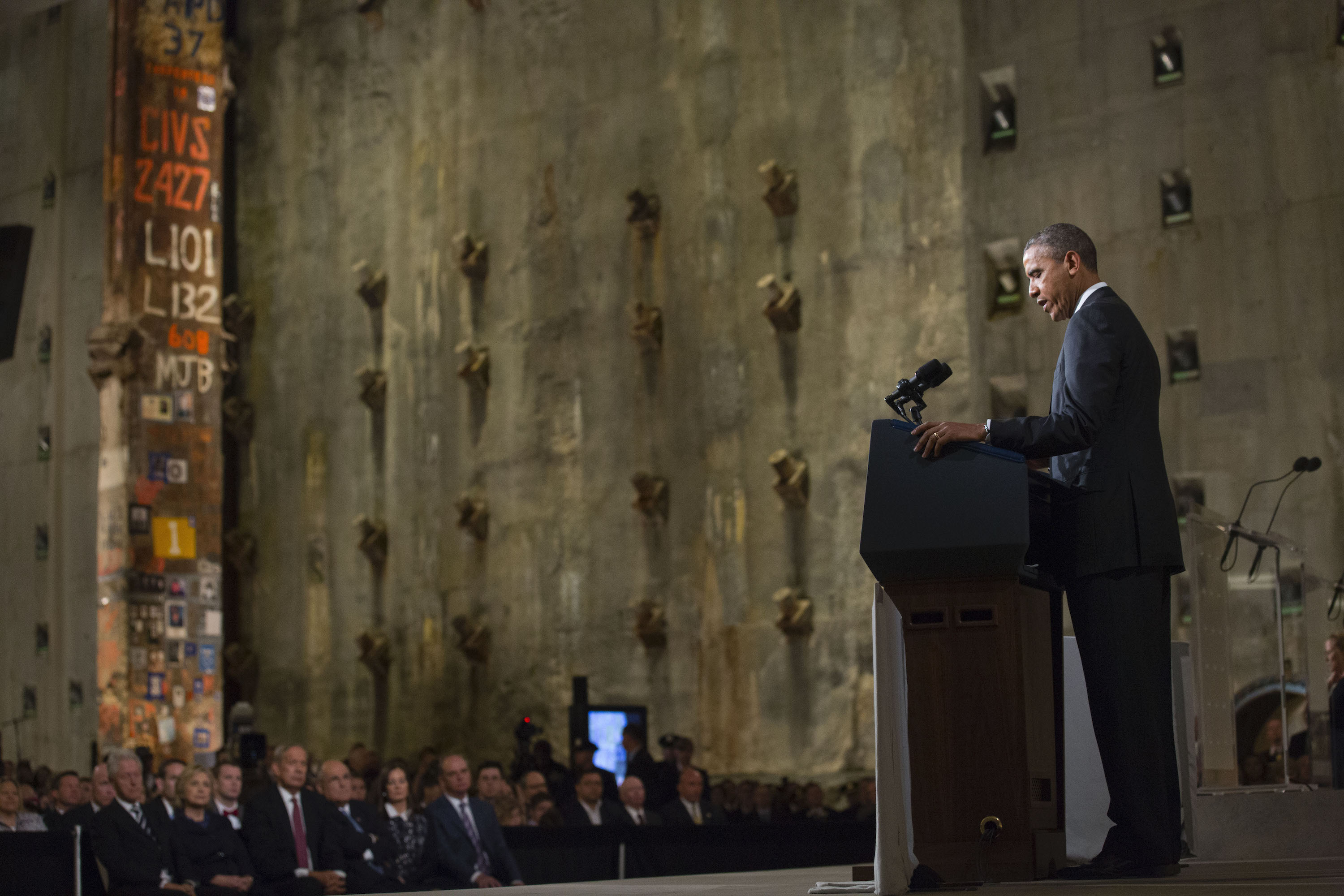 President Barack Obama speaks in Foundation Hall at the dedication of the 9/11 Memorial Museum on May 15, 2014. Former President Bill Clinton, Secretary of State Hillary Clinton, former New York Governor George Pataki, former Mayor Rudy Giuliani, and others watch on with the Last Column and slurry wall behind them.
