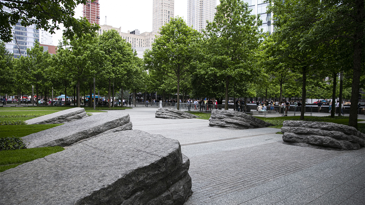 Six stone monoliths border the pathway of the 9/11 Memorial Glade. There are three monoliths on each side of the path. Trees with bright green leaves stand to the left and right and also off in the distance.