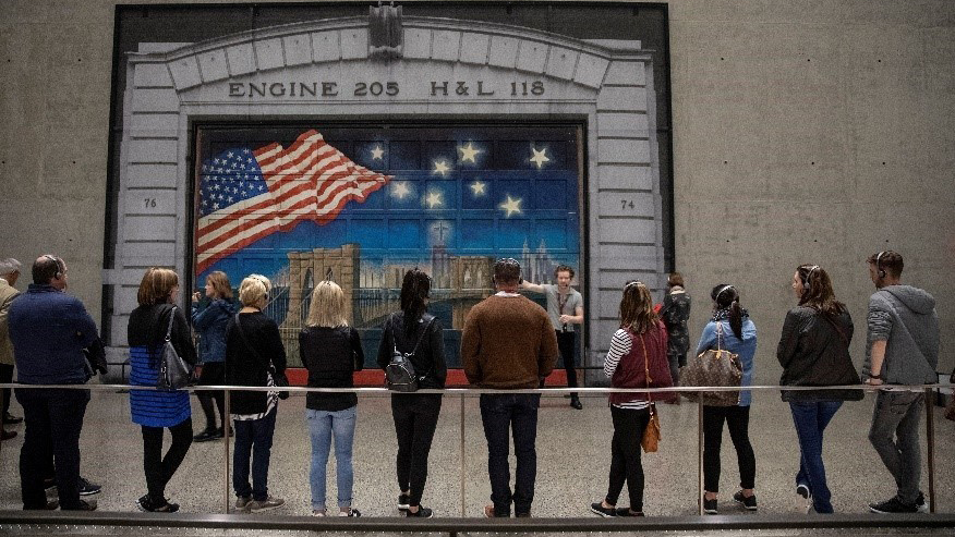 Ten visitors leaning on the railing, facing a young male tour guide explaining about a mural painted on the firehouse door behind him. The mural shows the skyline of lower Manhattan's buildings along the river with a bridge spanning the river. A rippling large American flag and 8 bright stars dominate the evening sky.