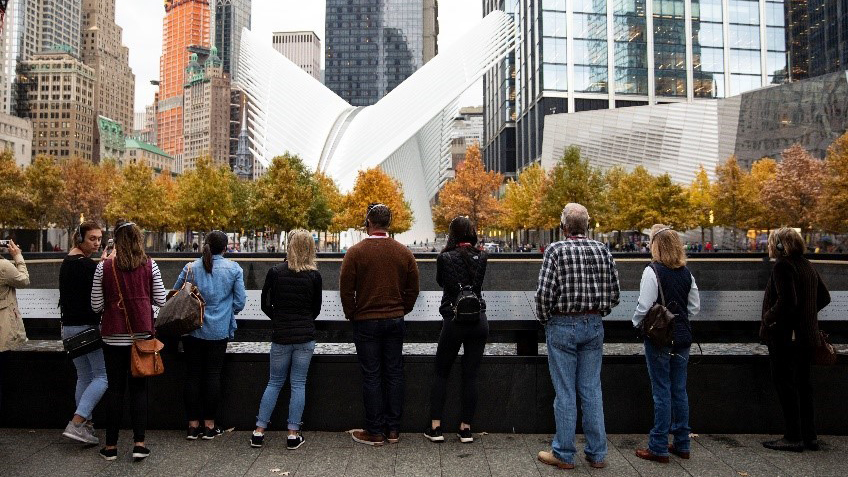 Visitors in autumn clothing stand beside the North Tower reflecting pool as they face towards the Oculus, a transportation hub with a white, winged design. The Oculus rises above fall-colored trees on the Memorial and is surrounded by the eclectic skyscrapers of lower Manhattan.