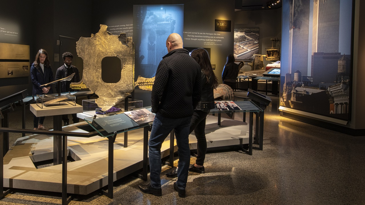 Artifacts from September 11, including a fire truck and pieces of an airplane, are on display at the Historical Exhibition. A lit image of the burning Twin Towers stands out at the center of the room. Other display areas and interactive screens are in the background.