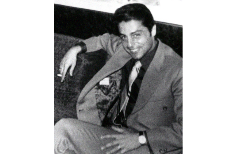 A black-and-white archival photo of a man in a suit and tie reclining with his arm propped up on the back of the chair he sits on. He smiles at the camera.