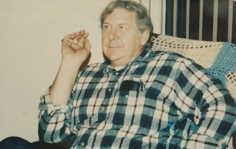 William Macko sits in a chair in a plaid shirt in this old photo.