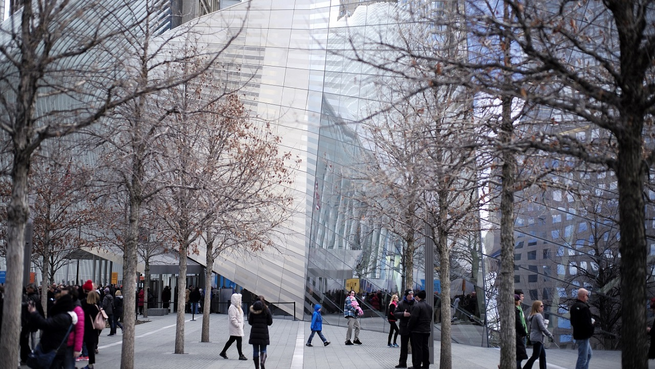 Visitors walk around the 9/11 Memorial plaza in front of the Museum's facade on a winter day. The trees are bare.