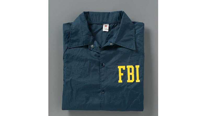"A navy blue windbreaker with ""FBI"" printed in yellow lettering on the left pocket rests neatly folded on a gray background."