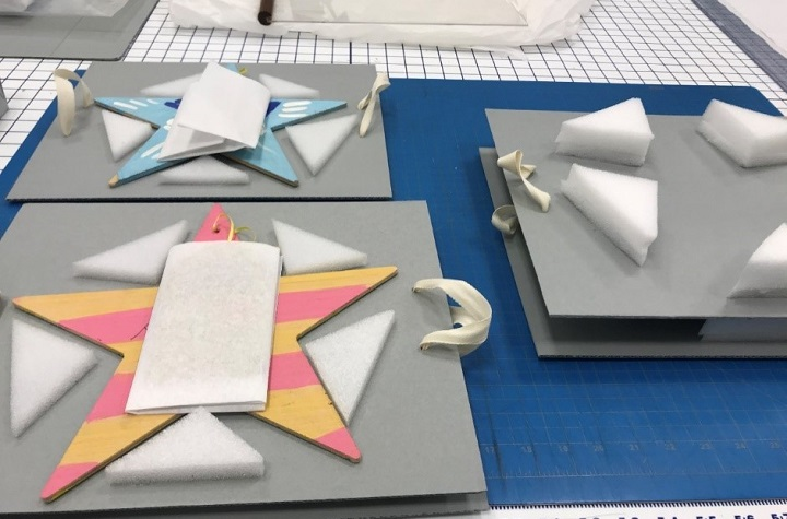 Multicolored wooden stars rest on gray cardboard waiting to be packaged.