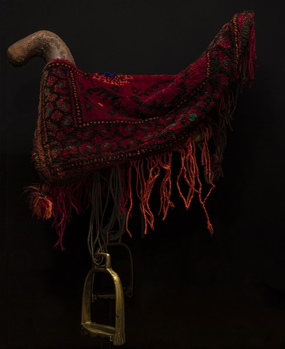 Saddle with metal stirrup pads draped in a short red rug decorated with patterns and fringes.