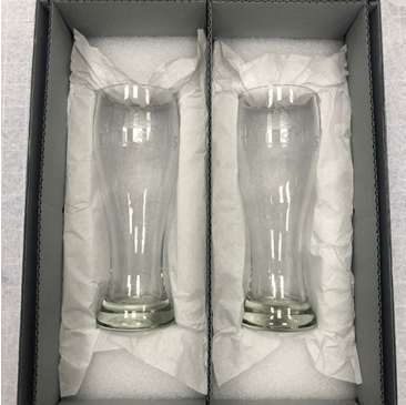 Two glass pint glasses sit side-by-side in a gray box resting on a bed of white tissue paper.