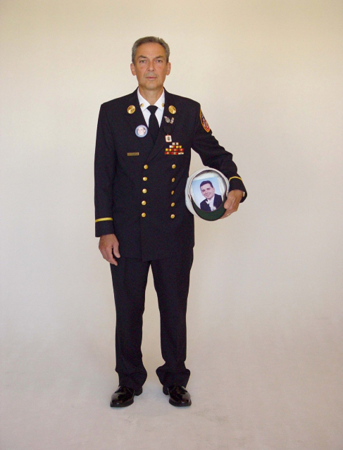 A man stands in FDNY dress uniform in front of a white background.