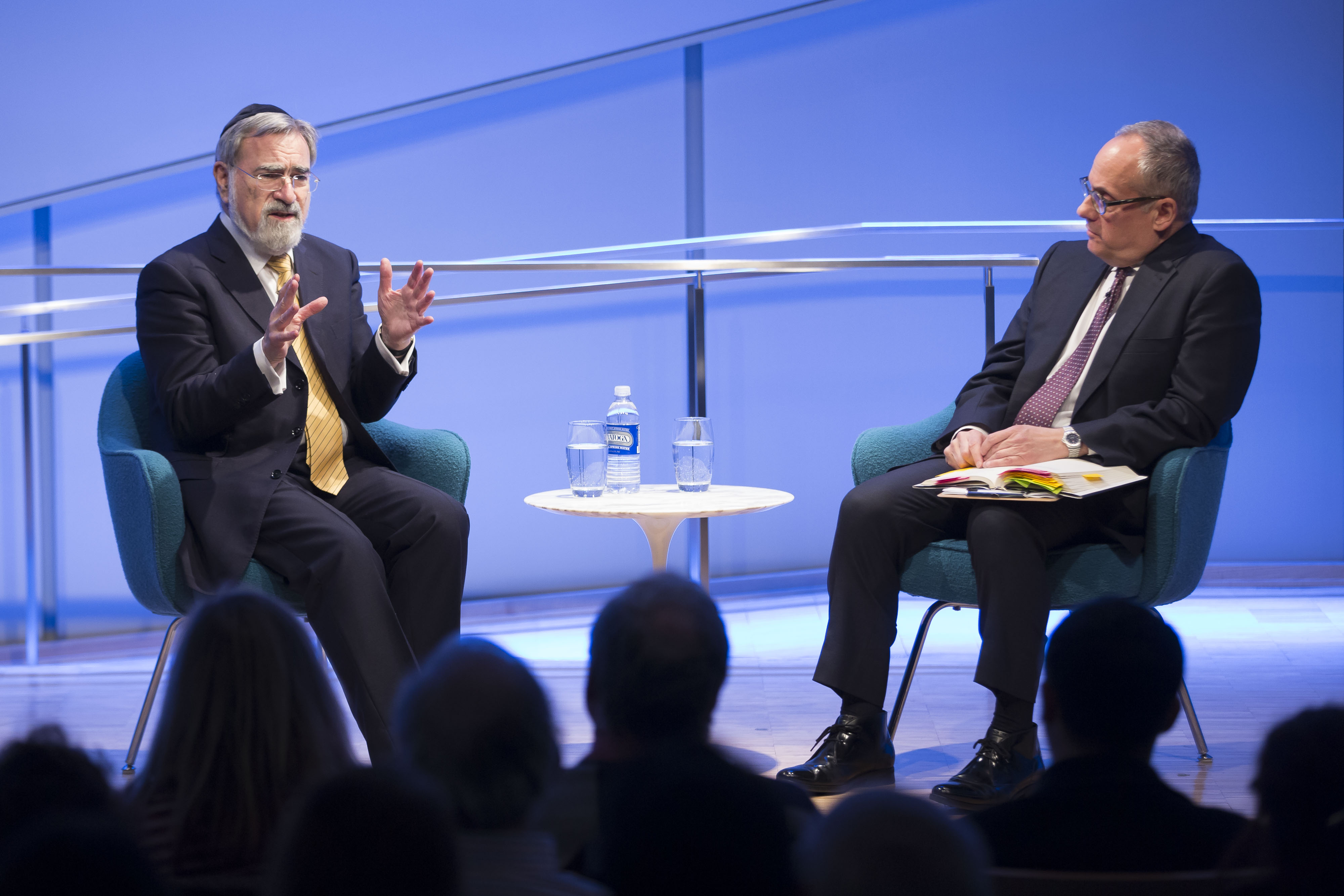 In this wide-angle shot, which shows audience members at the 9/11 Memorial Museum auditorium in in silhouette in the foreground,  the Rabbi Jonathan Sacks, who had retired as chief rabbi of the United Hebrew Congregations of the British Commonwealth when he visited in 2016, raises both his hands as he gestures in conversation with Cliff Chanin.