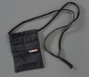 A black case with a neck strap, used for travel documents, is displayed on a gray background. It was worn by Flight 93 passenger Toshiya Kuge.