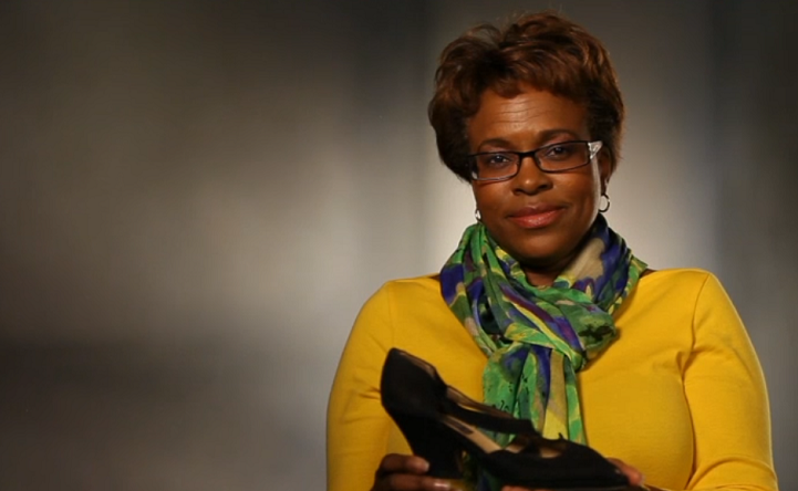 A woman in glasses and a yellow sweater sits in front of an illuminated gray background holding a high-heeled shoe.