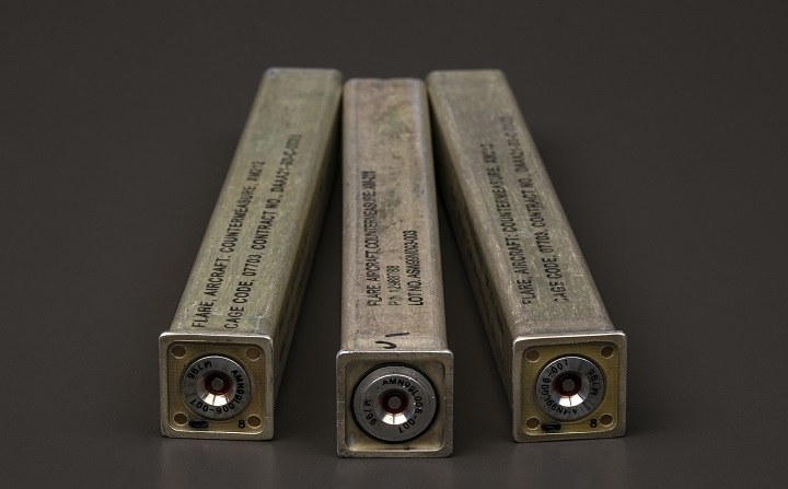 Three metal casings in the shape of square cylinder with indiscernible writing on them.