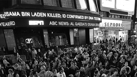 Back view photograph of a standing crowd in the middle of the street. News ticker above announces Osama Bin Laden Killed.