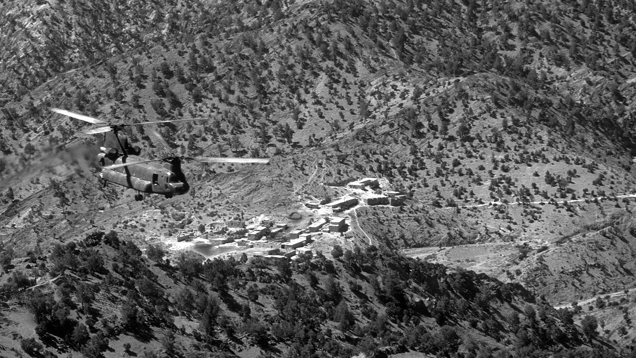 Birds eye view of a tandem rotor helicopter flying over a rocky mountain terrain.