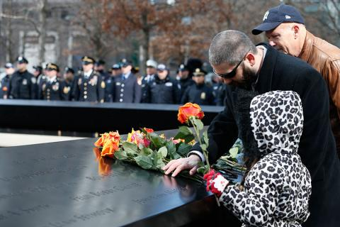 A young girl in a cheetah patterned jacket places yellow and red roses at a name on the Memorial during the ceremony commemorating the 23rd anniversary of the World Trade Center bombing. A man who is standing next to her is placing his hand on a bouquet of roses that have been placed nearby.