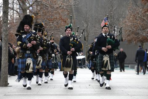Bagpipe and drum players affiliated with the NYPD and the Port Authority play at the 9/11 Memorial on a cloudy autumn day.