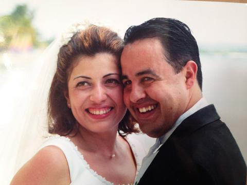 Carlos Lillo and his wife Haydee Cecilia Icaza-Lillo smile at their wedding in this close-up photo of their faces.