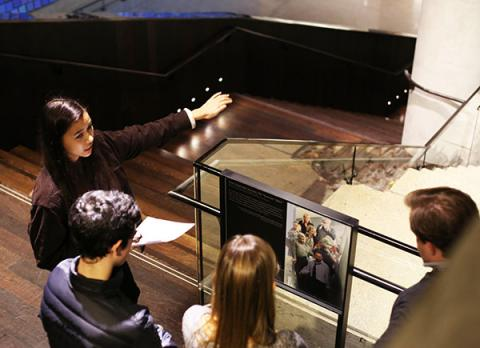 Student ambassador Annalee Tai leads a tour through the 9/11 Memorial Museum. She points to the Survivors' Staircase as several people watch on.