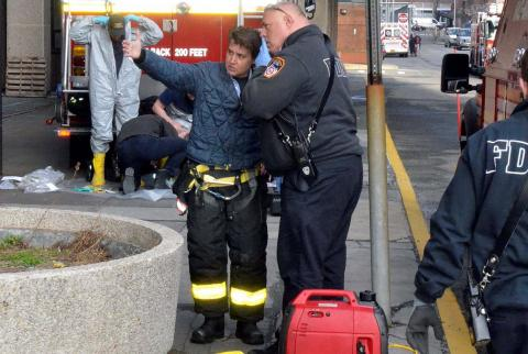 FDNY Lt. Adrienne Walsh wears bunker gear as she speaks to a man in an FDNY jacket while standing on the street and pointing at something out of view.