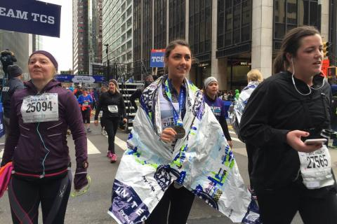 Katelyn Mascali shows of a medal that's around her neck as she takes part in the New York City Half Marathon. She is surrounded by other runners taking part in the event.