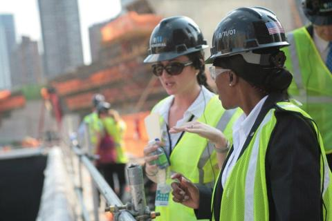 Allison Blais gives a tour of the Memorial pools during the period of construction. She and another woman, both in yellow vests and hardhats, speak beside the construction site.