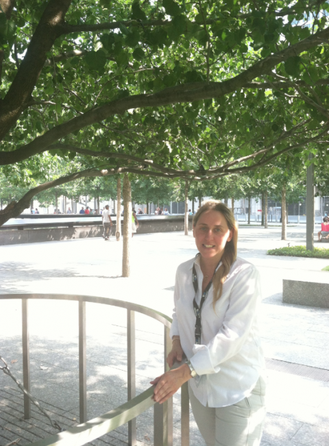 Volunteer Catherine Nadal stands in the shade of the Survivor Tree on the 9/11 Memorial plaza. Visitors to the Memorial can be seen beside a reflecting pool behind her.