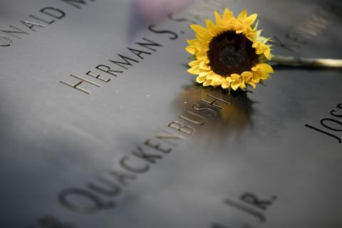 A yellow sunflower sits beside a name at the 9/11 Memorial.
