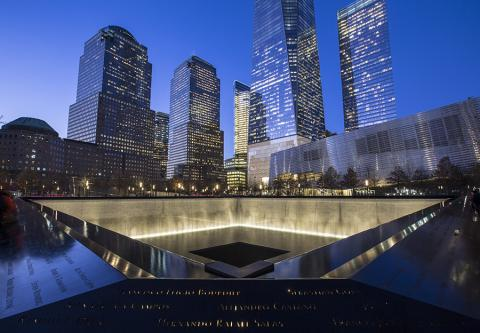 The south pool of Memorial plaza is lit up on a blue, cloudless evening in lower Manhattan.