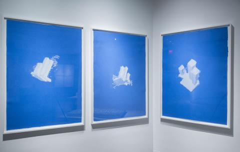 "Three works from artist and sculptor Christopher Saucedo's ""World Trade Center as a Cloud"" series are framed and displayed on a wall. The works are blue and white and were created by pressing wet layers of white linen with isometric drawings of the World Trade Center onto handmade blue-pigmented cotton pulp."
