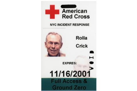 "An access badge belonging to Rolla ""Bud"" Crick is displayed on a white surface. The badge features the logo of the American Red Cross across the top of it. The bottom of the badge reads, ""Full Access and Ground Zero."""