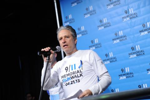 Jon Stewart speaks at a microphone while wearing a 9/11 Memorial 5K Run and Walk shirt.