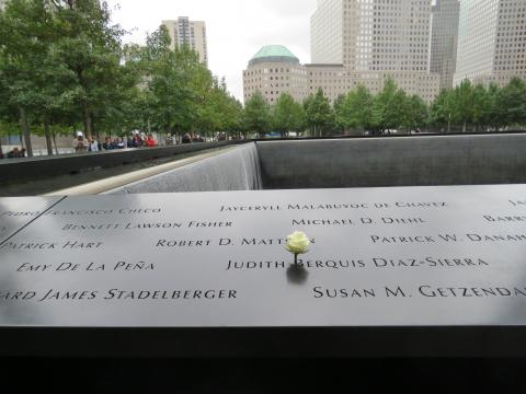 A white rose stands at the name of Judith Diaz-Sierra on the 9/11 Memorial.