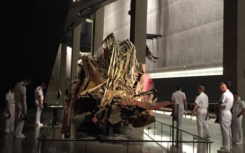 Members of the U.S. Navy look at the destroyed fire engine, Ladder 3, at the 9/11 Memorial Museum.