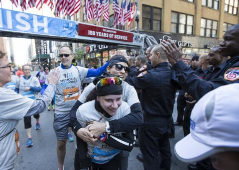 Runners embrace and give high-fives as they cross the finish line at the 9/11 Memorial 5K Run and Walk.