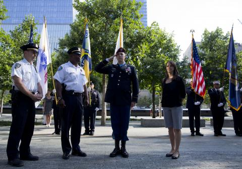 Medal of Honor recipient Ryan Pitts salutes as he stands in front of a color guard at Memorial plaza. Pitts is wearing a formal military outfit and is standing beside a woman and two uniformed police officers. Several trees on the plaza are behind him, as is One World Trade Center.