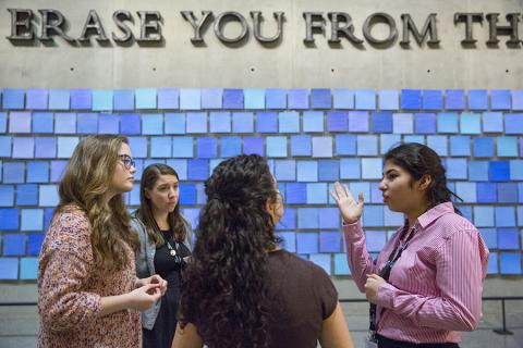 "A young woman practices giving a tour in front of artist Spencer Finch's installation, ""Trying to Remember the Color of the Sky on That September Morning,"" in the 9/11 Memorial Museum. Three women watch her as she practices the tour."