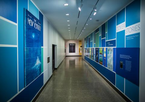 "The exhibition ""Cover Stories: Remembering the Twin Towers on The New Yorker"" is seen in a part of the Museum. Covers from past New Yorker issues are prominently displayed along two walls and on a distant wall."