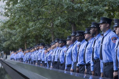 A probationary class of FDNY EMTs stands in front of a reflecting pool at the 9/11 Memorial.