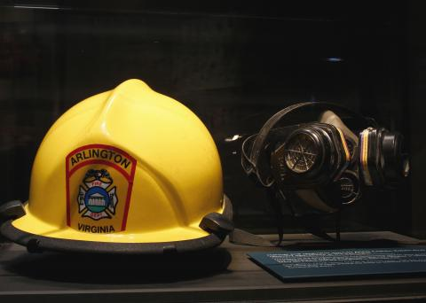 A helmet and respirator are seen in a glass display case at the Museum. The yellow helmet reads Arlington, Virginia, Fire Department.