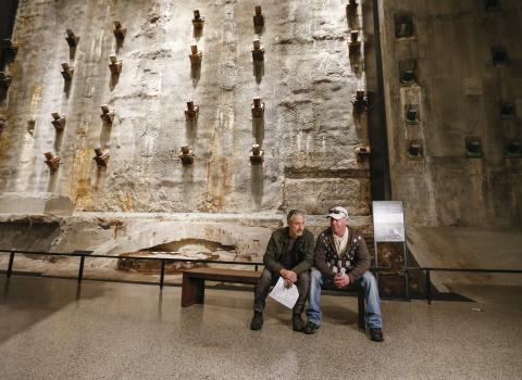 9/11 Memorial board member Jon Stewart and 9/11 responder and founder of the Fealgood Foundation John Feal sit on a bench next to the slurry wall in the Museum's Foundation Hall.