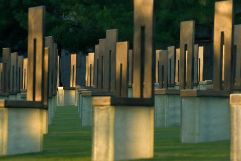 Sculptures of empty chairs fill a grassy field at the site of the Oklahoma City National Memorial and Museum. Sunlight passes through the chairs.